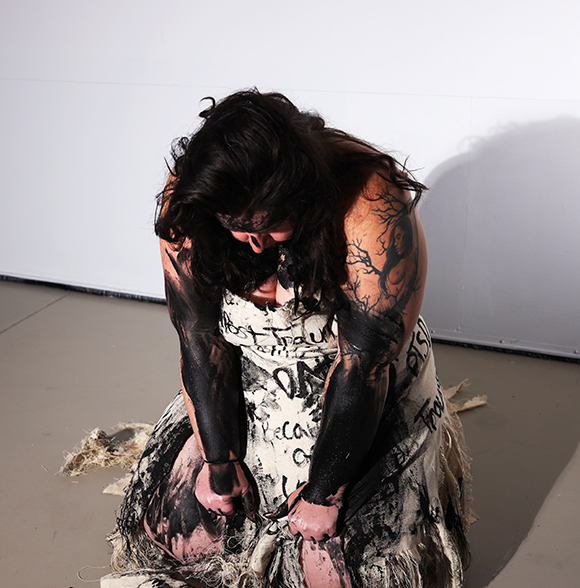 Artist kneeling down in paint covered dress during performance