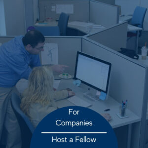 A photo of a woman sitting in front of a computer while a man standing next to her gestures at the screen. Photo has a blue tint over it and the words 'For Companies host a fellow' in a blue semicircle at the bottom center.