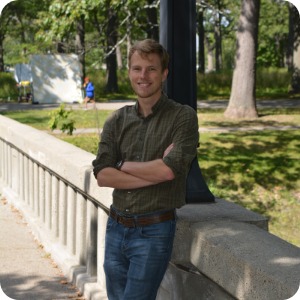 A young blond man in a green button down shirt with the sleeves rolled up leans against a concrete railing with a lamp post visible behind him.