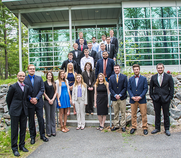 A group of college-age students dressed in business attire stand on the steps outside of a building in late spring.