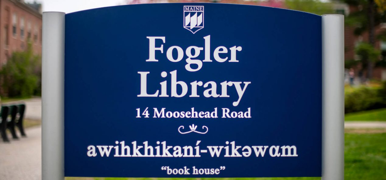 """sign for Fogler Library with Penobscot language phrase translated as """"book house"""""""