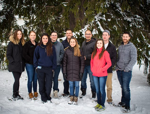 Maginnis lab photo taken on a snowy December day in front of a snow-covered evergreen. Maginnis lab made up of Dr. Maginnis, 4 graduate students, and 5 undergraduates.