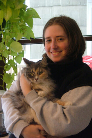 caucasian woman wearing a scarf holding a cat