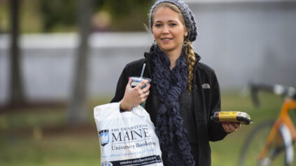 using your MaineCard off campus - student with takeout food and bookstore shopping bag