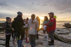 Students and the instructor gather together on the rocky shore at sunset.