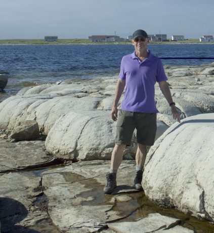 Picture of Andy Thomas standing on rocks on the shore.