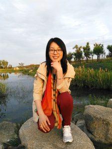 Photo of Lisha Guan on a rock near a pretty pond.