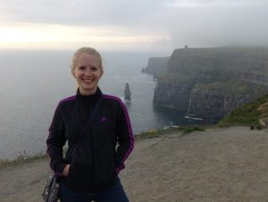 Picture of Brianna King on a foggy day at rocky cliffs overlooking the ocean.