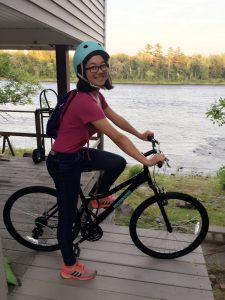 Picture of Shuling Chen on a bicycle near a river.