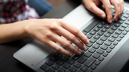 hands typing on laptop