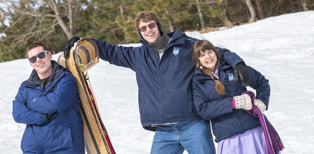 three umaine students smiling while holding sled