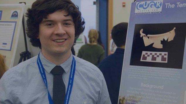student in front of research poster at conference