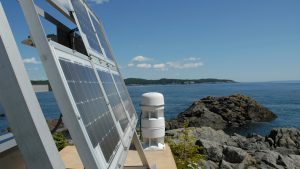 Solar panels on cement platform on rocky outcrop looking out to ocean and island on Maine coast