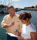 woman interviewing man in front of harbor