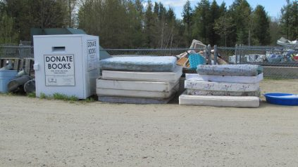 Image of book donation bin and discarded mattresses