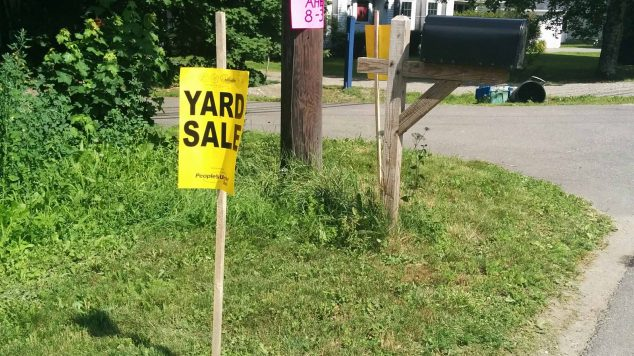 "Image of a lawn with a yellow sign that reads ""yard sale"""