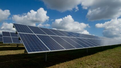 solar panels in field with sky and clouds