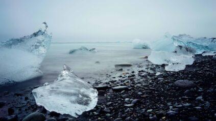 melting ice blocks along dark colored shore