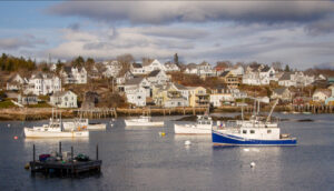 Harbor in Stonington, Maine, looking onshore from the water, with fishing boats in foreground and town behind