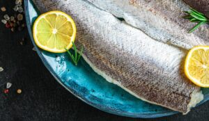 Raw hake fish fillet on turquoise plate with lemon slices on black background