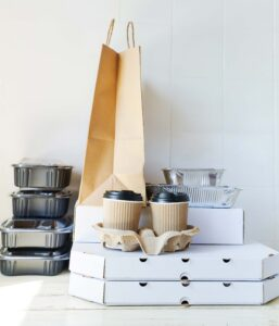 Variety of food takeout containers on counter in front of white background