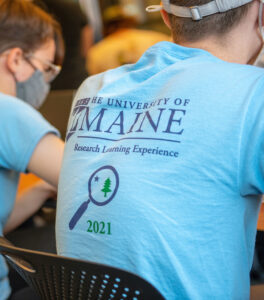 Back of student wearing blue tee shirt that says University of Maine, Research Learning Experience 2021
