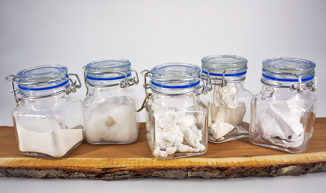 clear jars containing samples of white nanocellulose lined up on a piece of wood