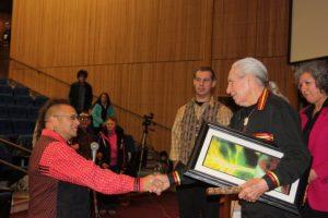 Gkisedtanamoogk giving Chief Oren Lyons a Painting