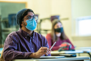 Student with face mask listening to his professor in class
