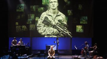 Man on stage with the image of a U.S. soldier behind him