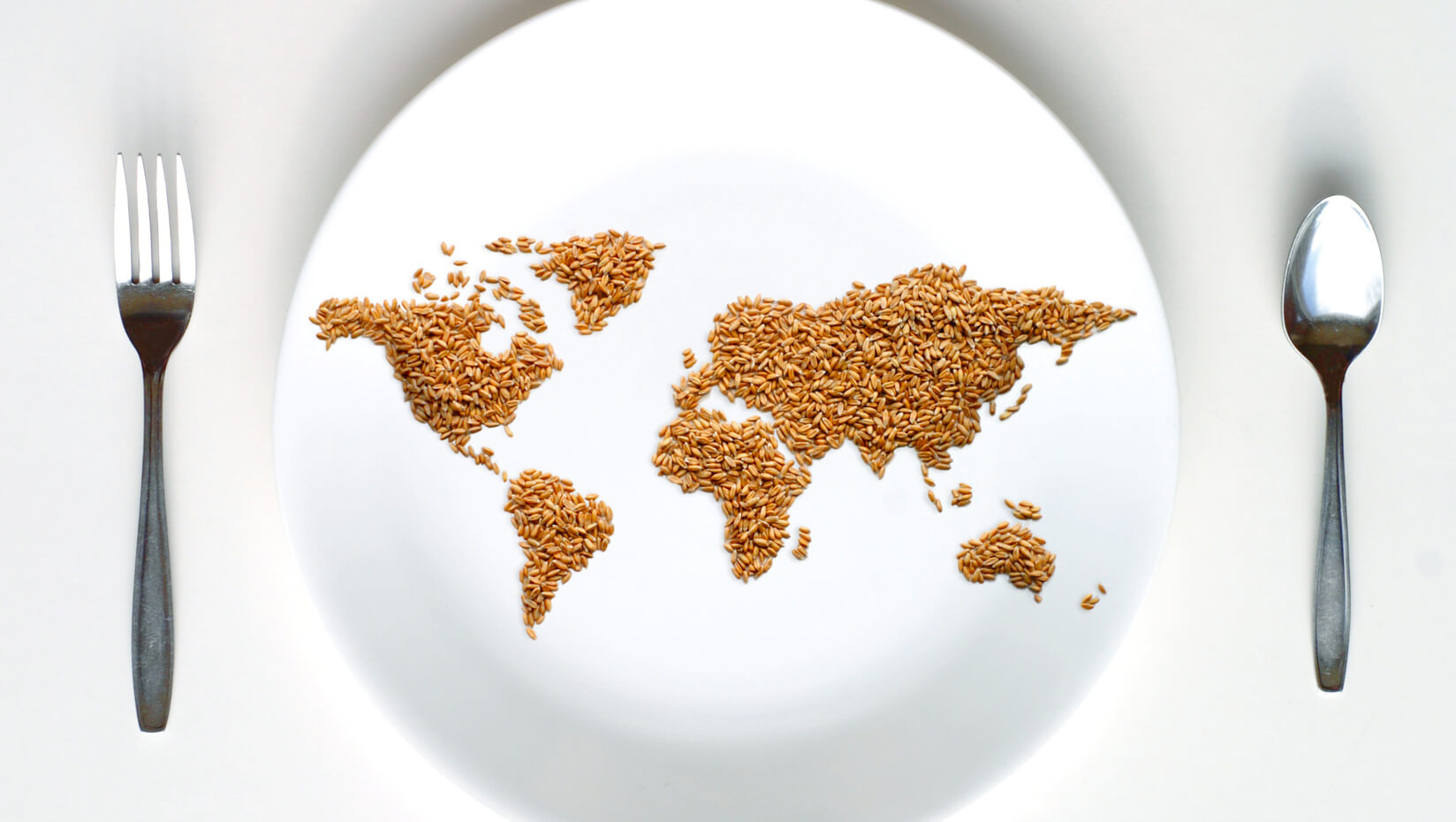 map of the world made of grain on a plate with a fork and spoon