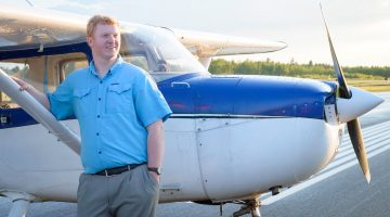 UMaine student stands in front of an airplane