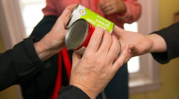 Hands accepting canned goods