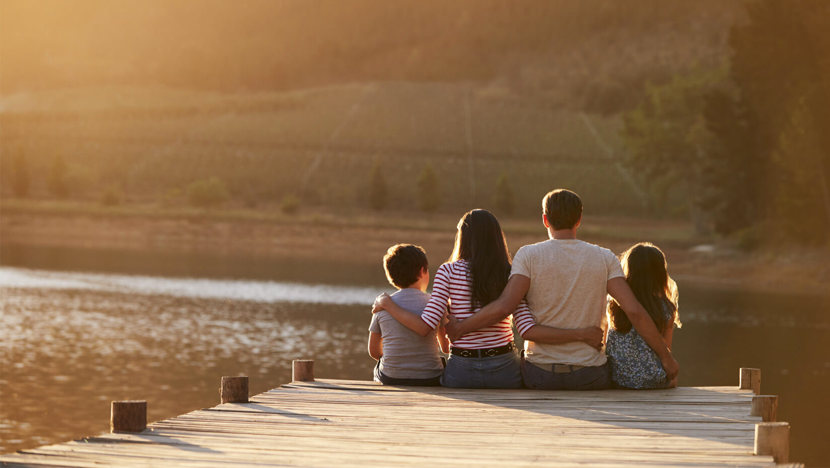 Family sitting on the end of a dock