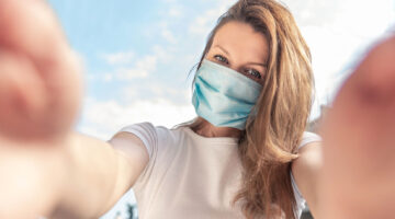Woman taking a selfie while wearing a face mask