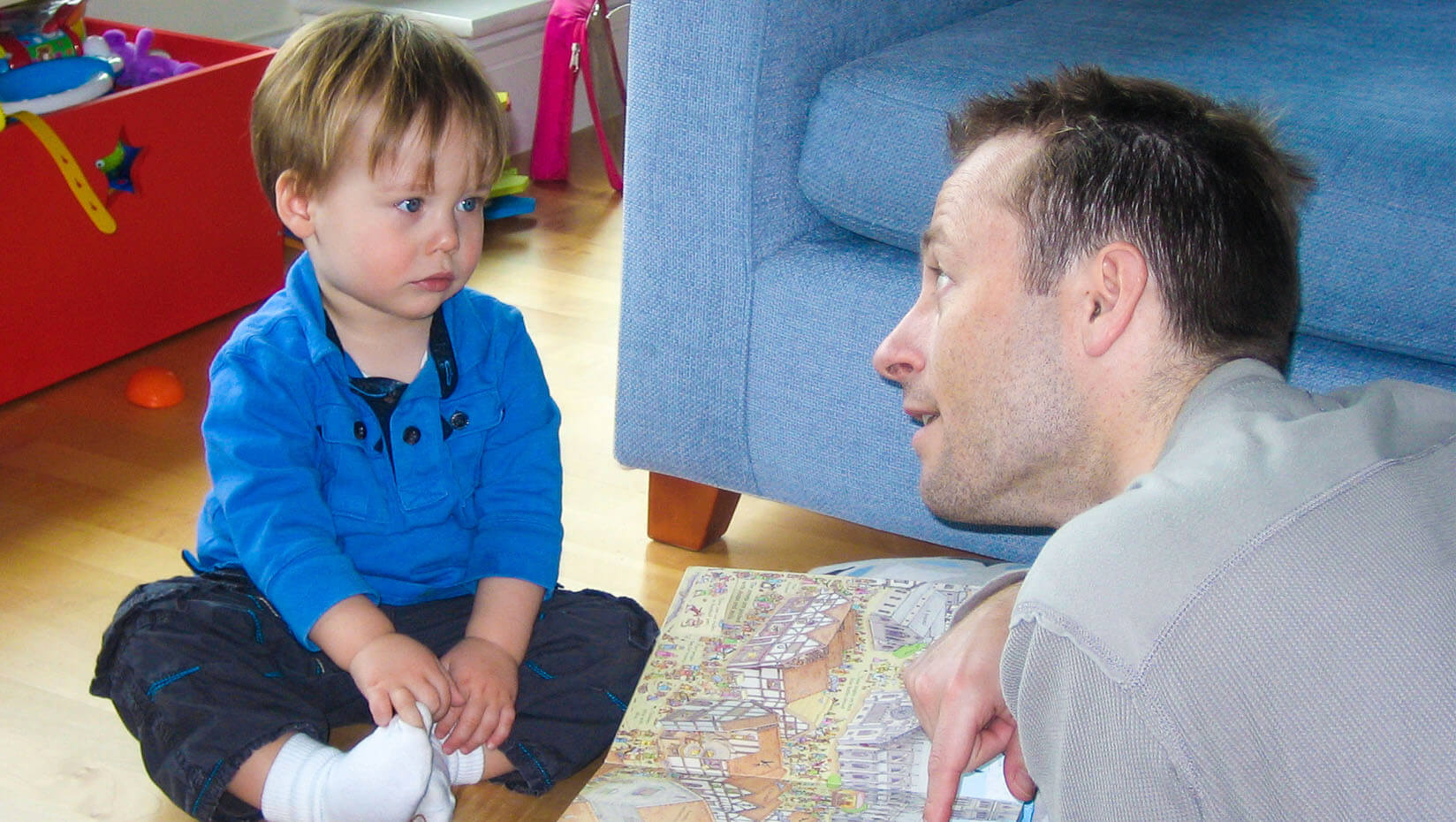 Toddler looking at a book with a man
