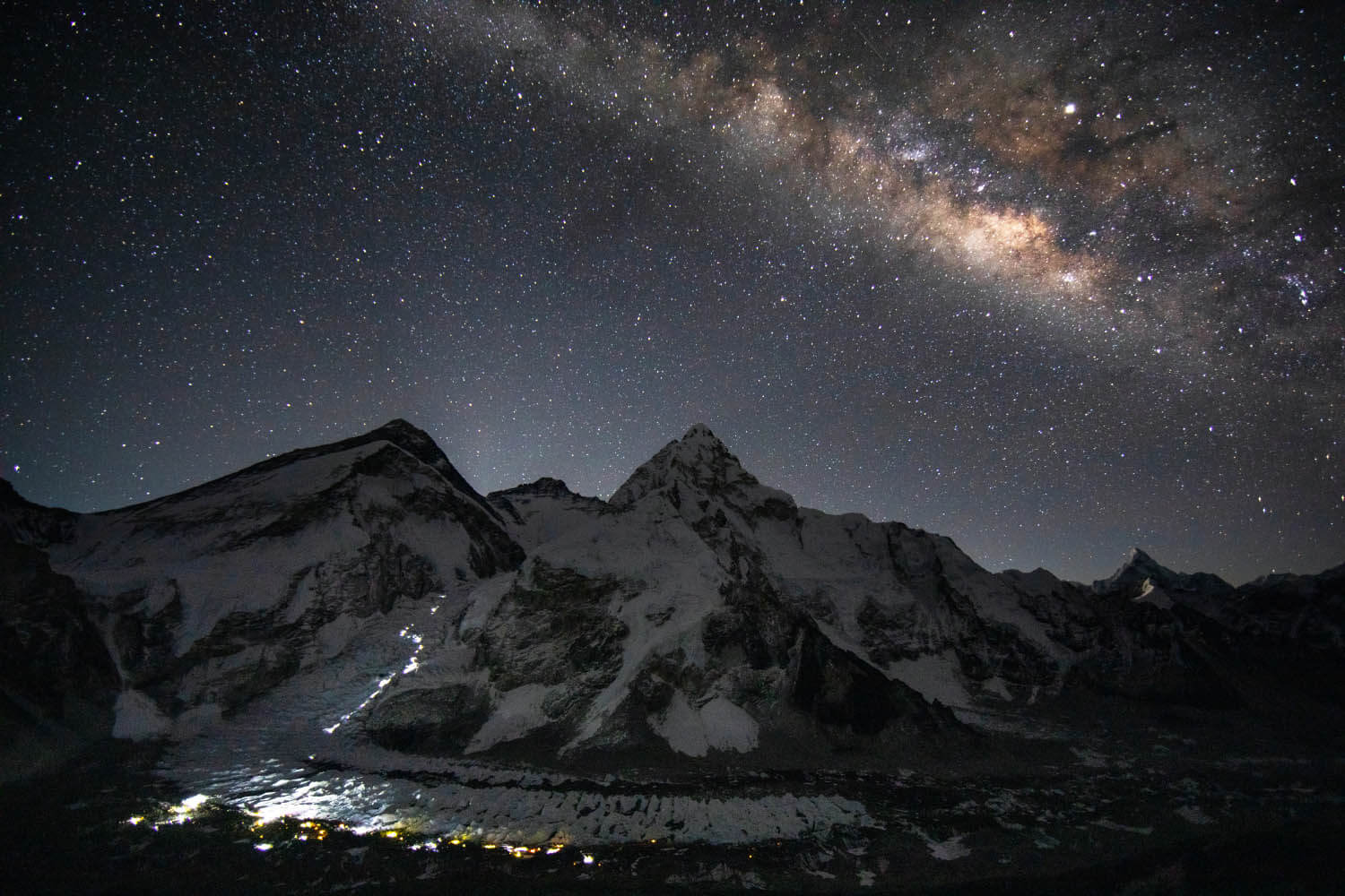 View of Mount Everest illuminated by the stars and climbers' lights