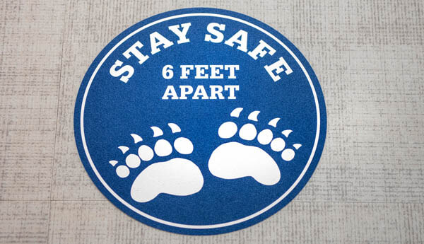 A floor sticker that says stay safe 6 feet apart