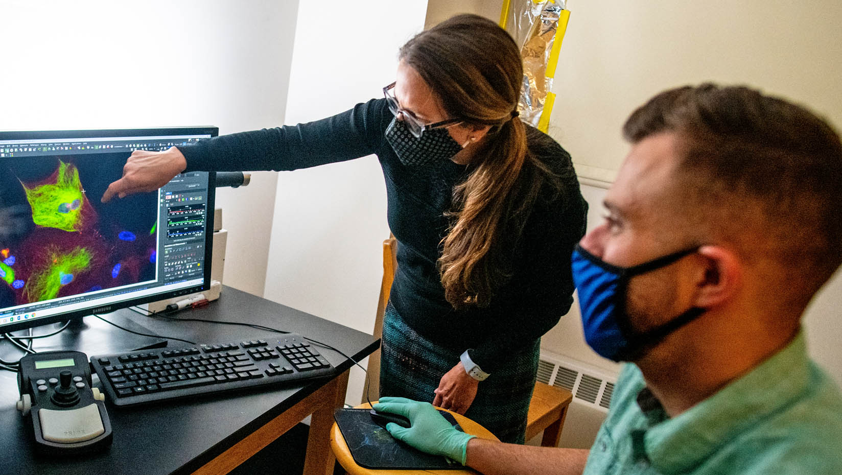 Melissa Maginnis points to a computer screen while a masked man looks on