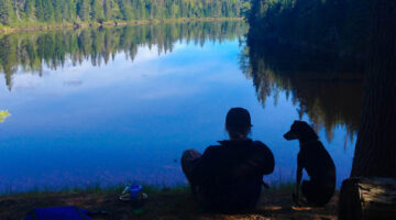 Michelle Moschkau sits on the edge of a lake with a dog