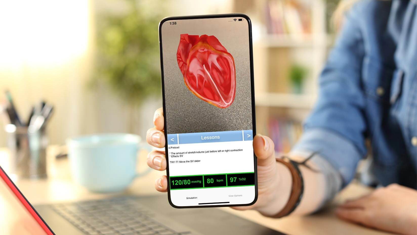 A student holds a smartphone showing an illustration of the human heart