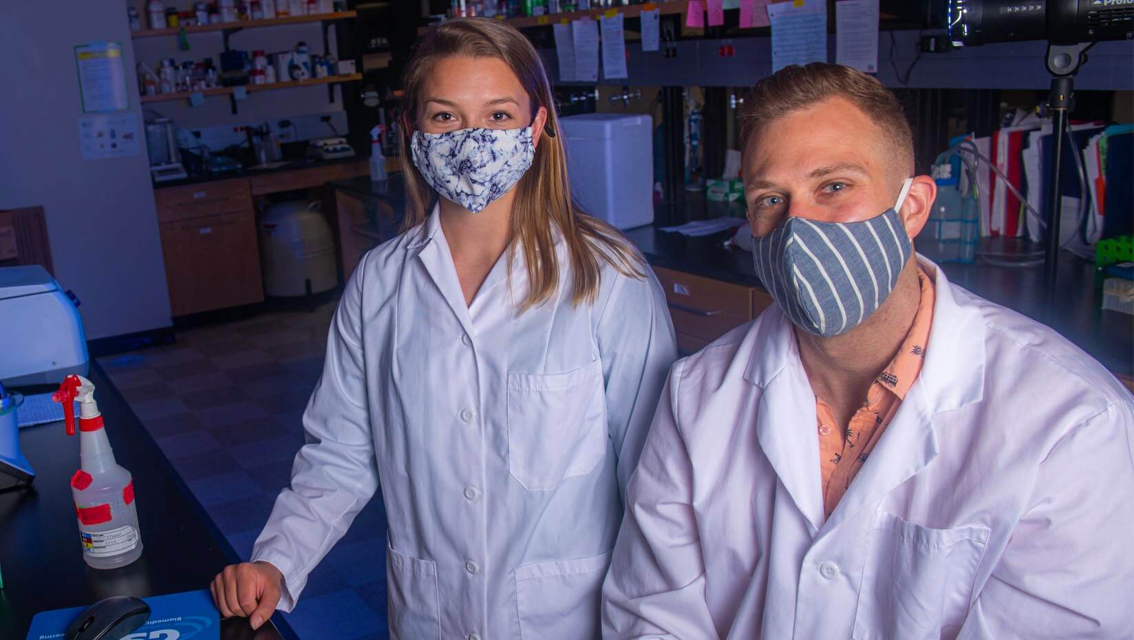 Two students wearing face coverings stand in a lab
