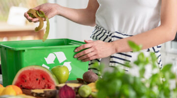 A woman puts food into a recycling container