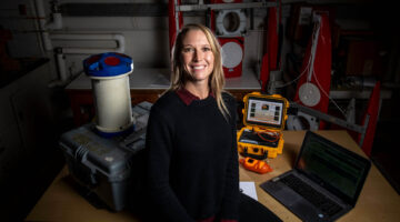 Lauren Ross sits in her lab in front of research equipment