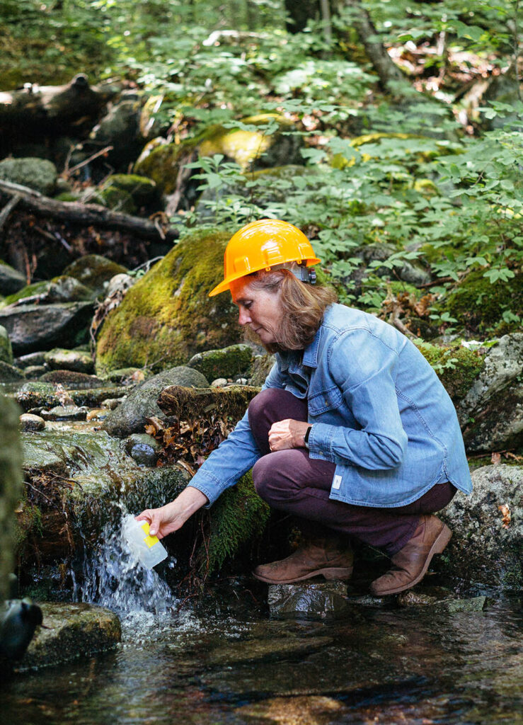 Woman collects water from stream