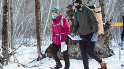 Two students snowshoe in the woods while holding maps
