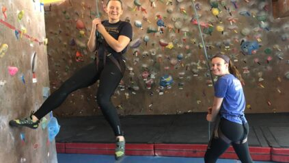 Two students rock climbing indoors