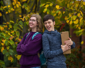 two smiling students with package in fall