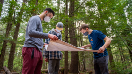 Three students wearing masks inspect a map in a forest.