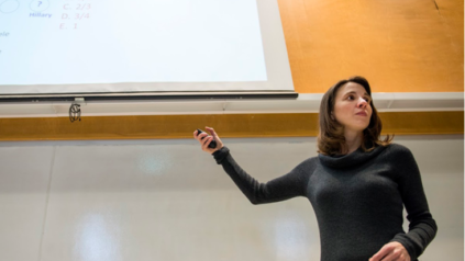 Female professor teaches, gesturing at projection screen in a classroom.